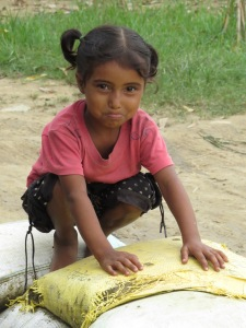 A happy girl sits atop sandbags that protect her house.
